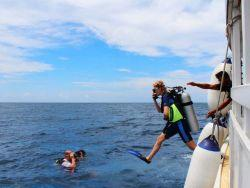 divers-jumping-into-crystal-clear-Maldives-sea-from-diving-dhoni